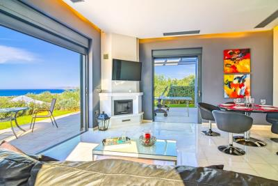 Villas-fo-sale-in-Platanias-Chania-Crete-living-area-with-sea-views-and-fireplace